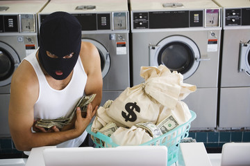 Man in ski mask with bags of money at laundromat