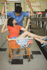 Couple with laundry cart at laundromat