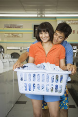 Couple with laundry hugging at laundromat