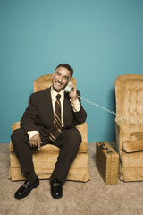 Portrait of businessman in chair talking on phone