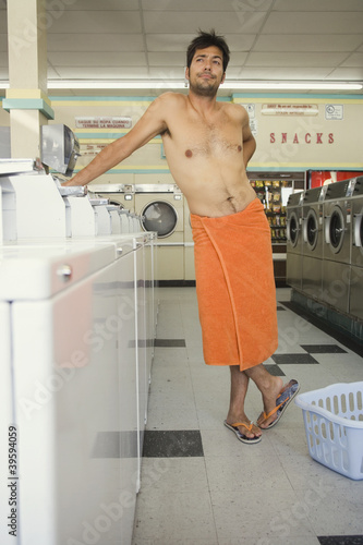 Man wrapped in towel standing in laundromat