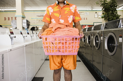 Mid section of man standing in laundromat with laundry