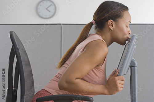 Woman in office kissing computer monitory