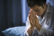 Man in pajamas holding rosary and praying