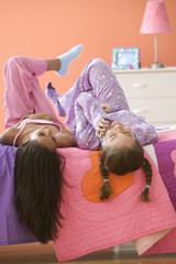 Two girls laying on bed talking on cell phone