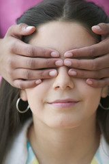 Girl with hands over another girls eyes