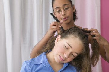 Girl styling another girl's hair