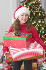 Portrait of girl in Santa hat in front of Christmas tree holding gifts