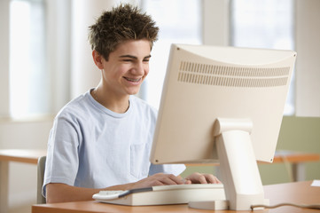 Teenage boy sitting in front of computer
