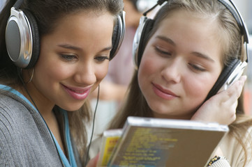 Close up of two teenage girls with headsets listening to music