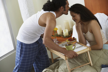 Man kissing woman as he serves her breakfast in bed