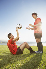 Two soccer players playing catch with ball