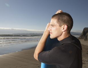 Profile of man in wet suit at beach with surf board