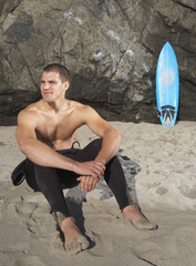 Man sitting in sand at beach with surf board