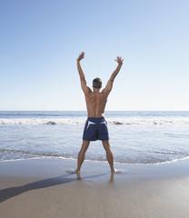 Rear view of man exercising at the beach