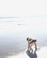 Rear view of boy digging in sand at the ocean