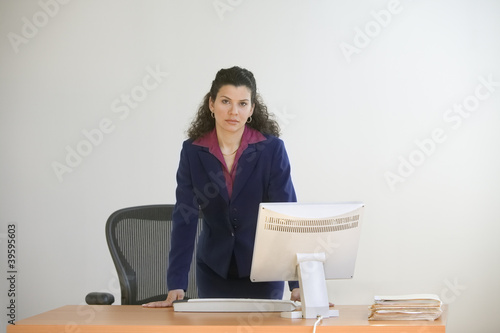 Businesswoman standing behind desk with computer