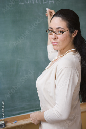 Portrait of female teacher writing on chalkboard