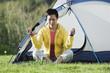 Woman sitting outside tent meditating