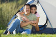 Portrait of father and daughter hugging outside tent