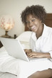 Portrait of woman in bed with laptop