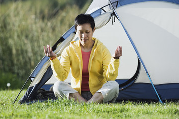 Woman sitting outside tent meditating