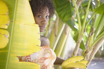 Portrait of woman in banana tree holding bananas