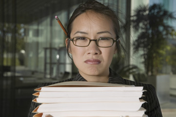 Close up portrait of frustrated businesswoman with stacks of files