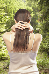 Rear view of woman standing in forest running hands through hair