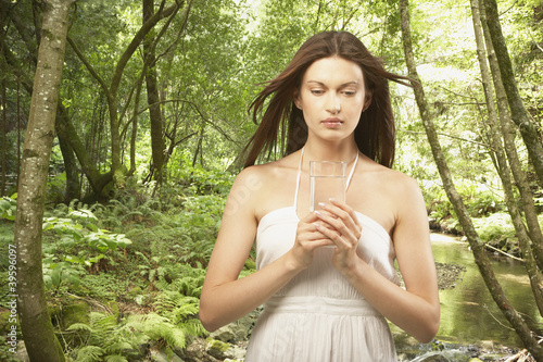 Woman holding glass of water in forest