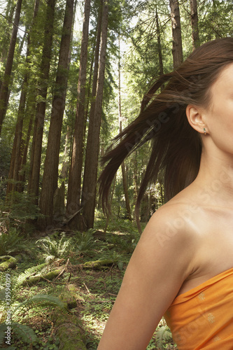 Woman's hair blowing in forest