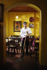Portrait of man mopping restaurant floor