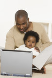 Father using laptop and holding baby daughter