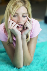 Young woman leaning on her elbows while thinking