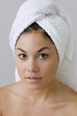 Woman posing for the camera with wearing a towel on her hair