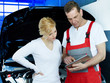 Mechanic and customer in a garage working with touchpad