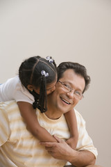 Young girl kissing father's cheek