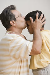 Father kissing son's forehead