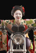 Asian woman in ethnic clothes driving a motorcycle