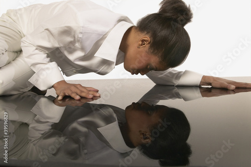 Young woman looking at her own reflection in the floor