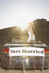 Bride standing in convertible with Just Married banner on the back