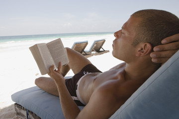 Bare chested man reading on a lounge chair at the beach