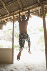 Young man hanging from doorway at the beach
