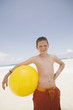 Young boy holding beach ball at the beach