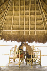 Couple kissing underneath thatch roof