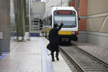 Businessman waving down a train