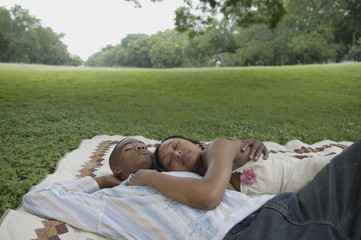 Couple relaxing on a picnic blanket outdoors
