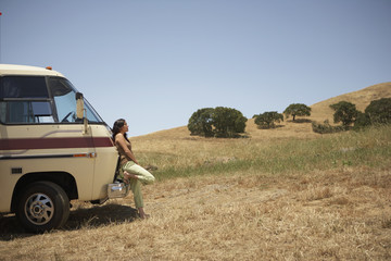Young woman leaning against a recreational vehicle