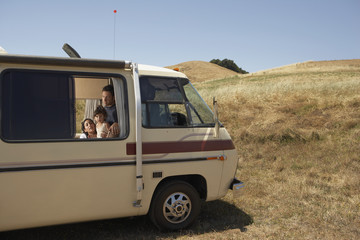 Family looking out of recreational vehicle window