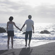 Young couple standing in water on beach